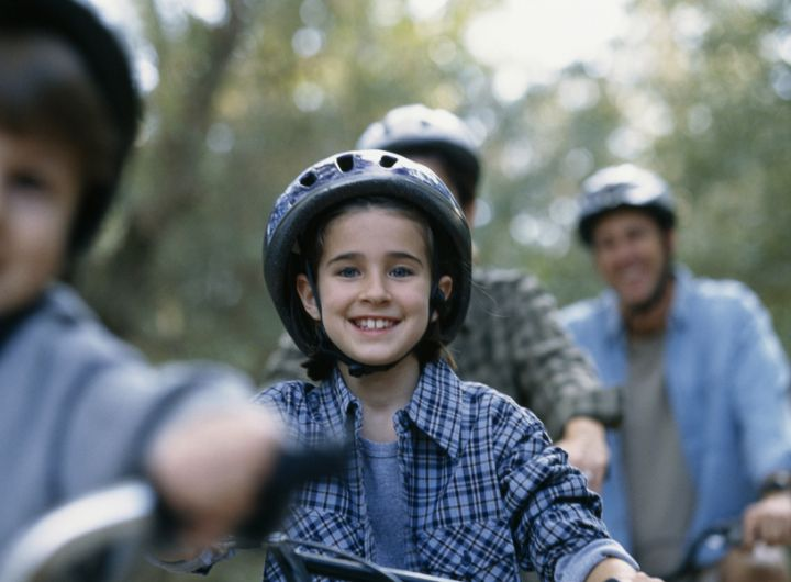 family riding bicycles through nature scene