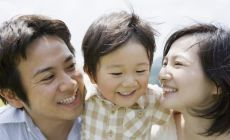 happy parents either side of toddler-age boy