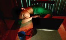 teenage boy lying slumped in front of computer at night