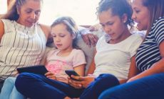 family sitting on couch talking - two children are looking at devices