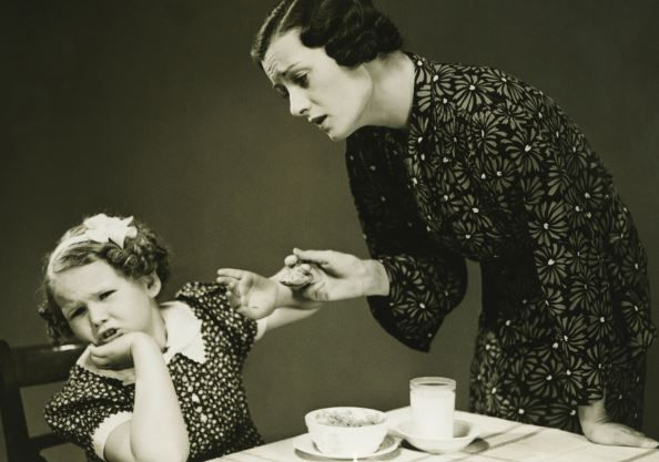 black and white 1930s mother tries to make child eat dinner