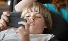 Boy playing on smart phone