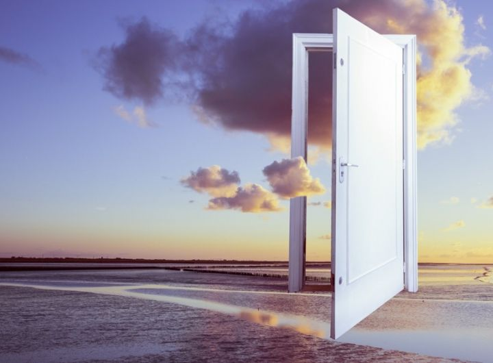 surreal image of floating door over the ocean at sunset